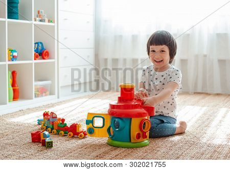 Child Playing With Colorful Toy Blocks On The Floor In The Room Little Girl Is Building A Tower At H