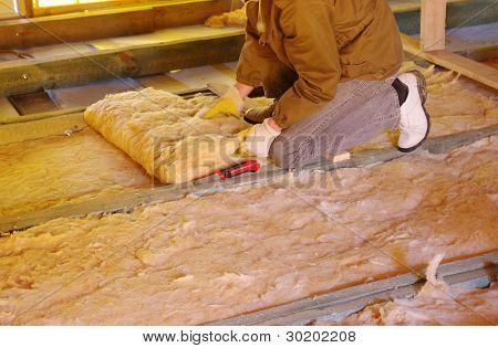 Trabalhador da construção civil isolamento térmico sótão da casa com lã de vidro