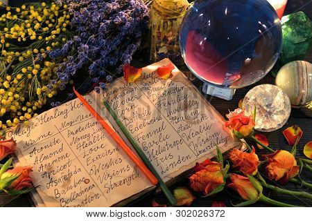 Open Witch Diary With Names Of Healing Herbs, Crystal Ball And Flowers. Wicca, Esoteric, Divination
