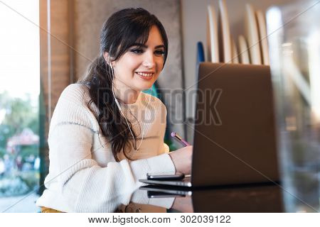 Portrait Of Young Woman Sitting At Table In Front Of Laptop. Girl Works On Computer Cafe, Checks E-m