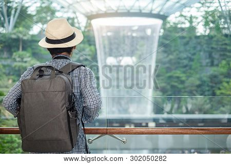 Young Man With Bag And Hat, Asian Traveler Standing And Looking To Beautiful Rain Vortex At Jewel Ch