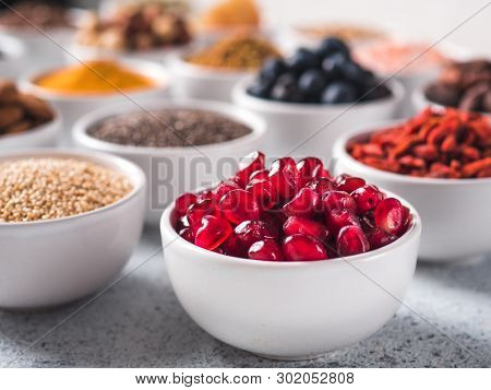 Pomegranate Or Grain Of Garnet In Small White Bowl And Other Superfoods On Background. Selective Foc