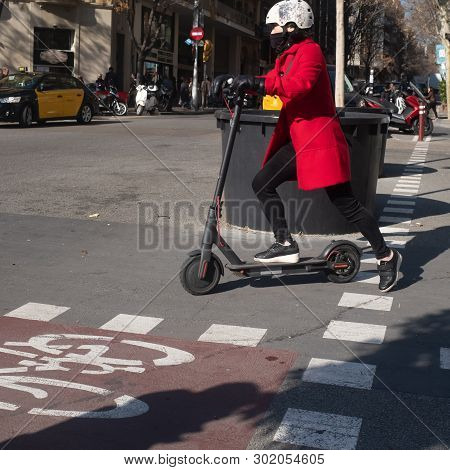 Barcelona, Catalonia / Spain - February-06-2019: Woman Driving An Electric Scooter With Helmet Aroun