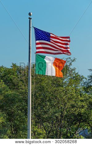 The American And Ireland Flags Waving On Pole On A Breezy Summer Day.