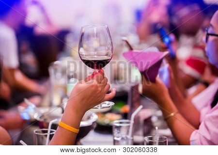 Group Of Unrecognizable People Toasting With Wine.