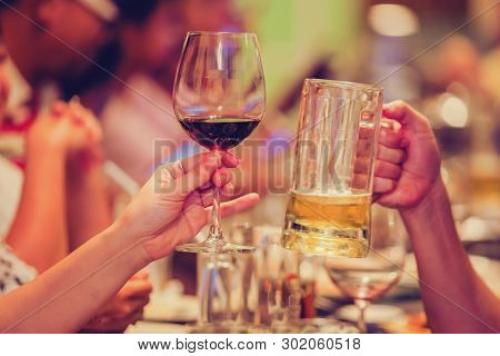 Group Of Unrecognizable People Toasting With Wine And Beer.