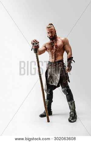 Serious Long Hair And Muscular Male Model In Leather Vikings Costume With The Big Mace Cosplaying Is