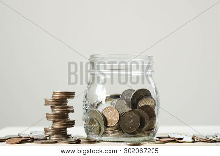 Closeup Coins Stacking Chart For With Glass Jar On Wooden Table And White Background.saving And Inve