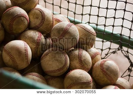 A Netted Basket Of Worn, Dirty, Practice Baseballs With Evening Light. Nostalgic.
