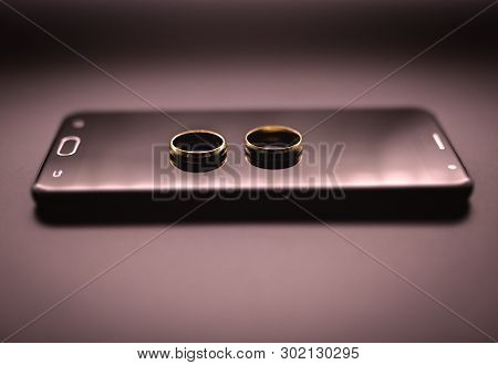 Concept Of Infidelity Or Virtual Betrayal Through The Smartphone. Golden Wedding Rings On A Mobile P
