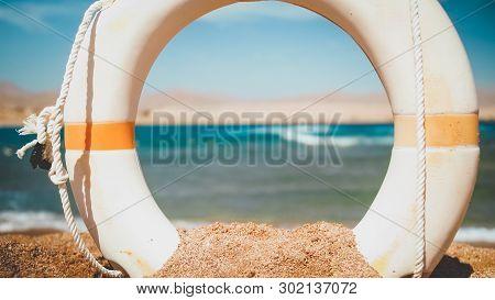 Closeup Image Of Beautiful Sea Beach And White Plastic Kife Saving Ring At Bright Sunny Day. Perfect