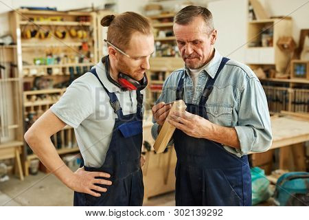 Waist up portrait of senior carpenter teaching apprentice  standing  in joinery workshop, copy space poster