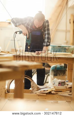 Portrait of red haired carpenter drilling wood while working in joinery lit by sunlight, copy space poster