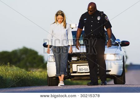 Policeman watching young woman walk in a straight line