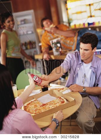 Young man passing cell phone in pizza parlor