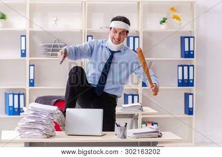Young injured male employee working in the office