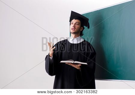 Graduate student in front of green board