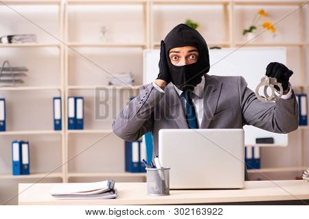 Male gangster stealing information from the office