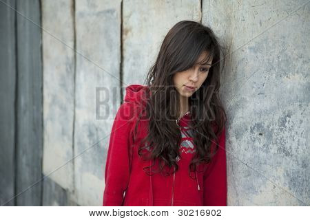 Teenage girl leaning against grunge wall with expression of sadness.