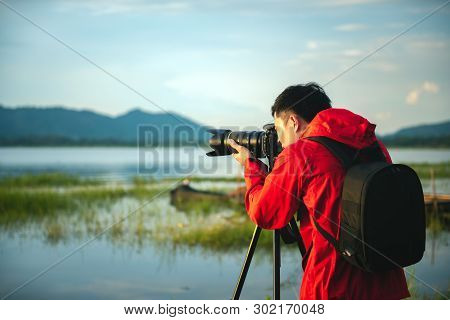 Travel Photographer Taking A Photo With Nature The Lake In Sunset With Camera On Tripod, Focusing At