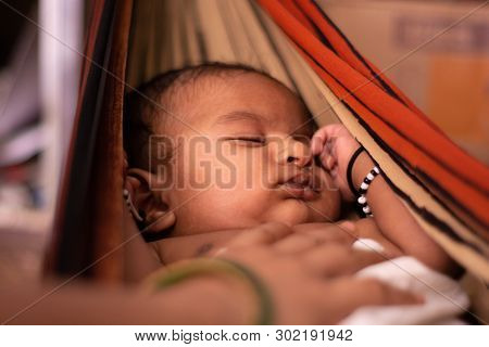 Closeup Of Cute Little New Born Baby Sleeping In Cradle Made Of Saree With Mothers Hand On Baby.