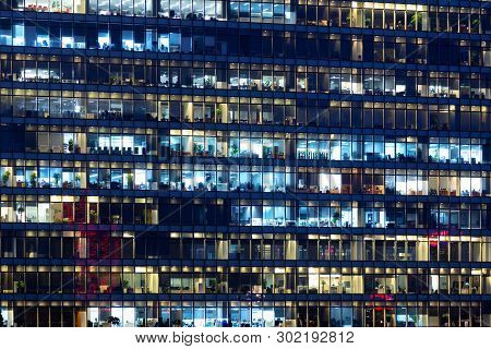 Office Building Exterior In The Late Evening With Interior Lights. Business People Working In The Ev
