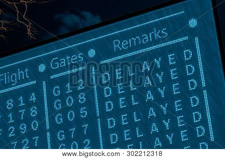 Delayed Flights Due To Bad Weather Concept. Airport Timetable Under Deep Rain With Lightnings And Da