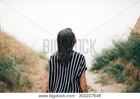 Stylish Hipster Girl Walking To Sea Between Sandy Cliffs With Grass At Sunset. Happy Young Boho Woma