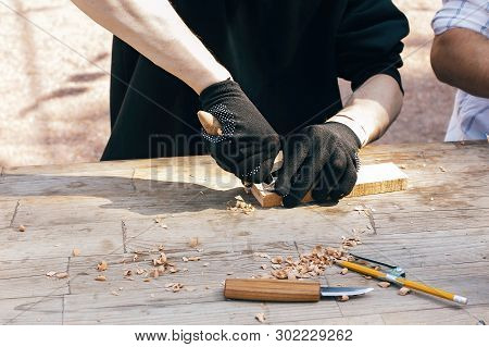 Wooden Workshop. Hands Carving Spoon From Wood, Working With Chisel Close Up. Process Of Making Wood