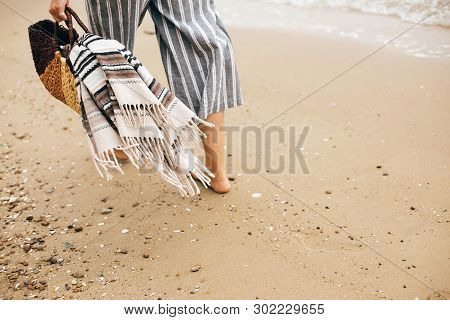 Stylish Hipster Girl Walking Barefoot On Beach, Holding Bag  In Hand, Closeup. Summer Vacation. Spac