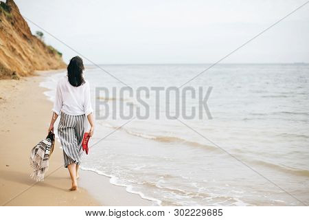 Stylish Hipster Girl Walking Barefoot On Beach, Holding Bag And Shoes In Hand. Summer Vacation. Spac