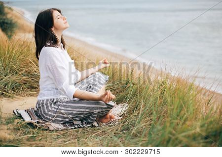 Yoga Day. Stylish Hipster Girl Sitting On Beach In Yoga Pose And Relaxing. Happy Boho Woman Practici