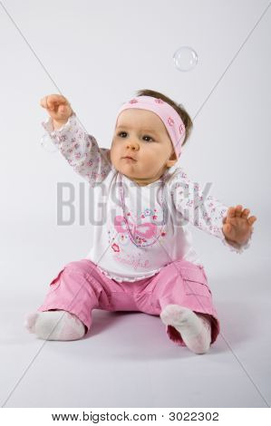 One Year Old Cute Baby Girl Trying To Catch Soap Bubbles.