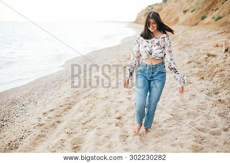 Stylish Hipster Girl Running On Beach At Sea And Smiling. Happy Boho Woman In Denim Jeans And Floral