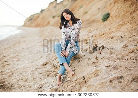 Stylish Hipster Girl Sitting On Beach At Sea. Happy Fashionable Boho Woman Relaxing At Sandy Cliff O