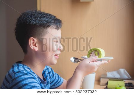 Young Asian Boy Holding Green Tea Roll Cake And Smiles