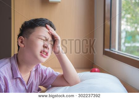 Young Asian Boy Sitting Near By The Window Having Headache In The Morning