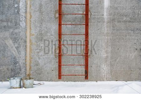 Old Metal Ladder On Wall Of Cement Building In Winter