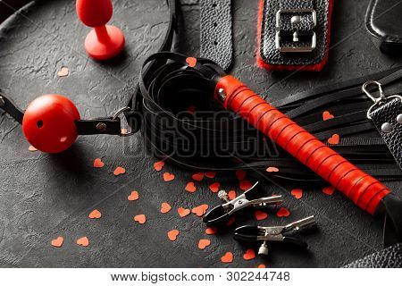 Bdsm Sex Toys For Adults. Small Red Hearts On Black Background Whip, Gag, Handcuffs And Leather Stra