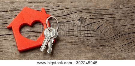 Wooden Red House And Keys On The Old Wooden Boards. Copy Space For Text
