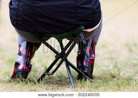 Weighty Butt Sitting On Small Folding Chair