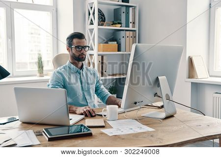 Inspired To Work Hard. Young Modern Businessman Working Using Computer While Sitting In The Office