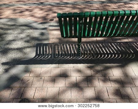 Steel Bench Under The Tree Shadow Of Foliage