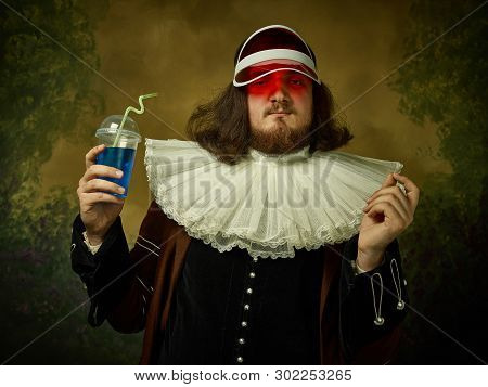 Young Man As A Medieval Knight In Red Cap On Dark Studio Background. Portrait Of Male Model In Retro