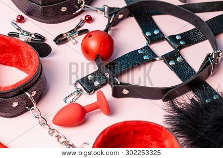 Set Of Erotic Toys For Bdsm. The Game Of Sexual Slavery With Handcuffs, Whip, Gag And Leather Straps
