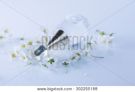 Perfume With White Flowers On Gray Table
