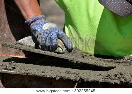 Concrete Worker Growls Wet Mud(concrete) On The Footings Of A New Construction Building Site.