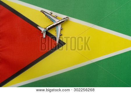 Plane Over The Flag Of Guyana, The Concept Of Travel And Tourism. Toy Plane On The Flag In The Backg
