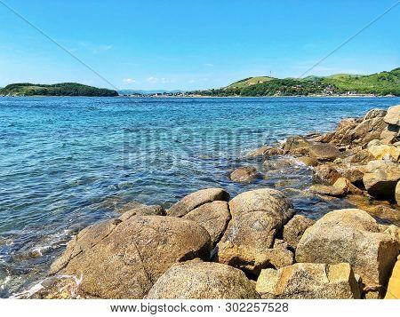 Beautiful Summer Day On A Rocky Beach Near The Transparent Sea