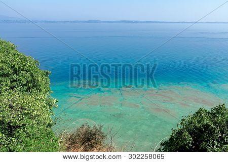 Beautiful Emerald And Calm Waters Of Lake Garda Near Sirmione Town, Italy. On The Horizon In The Fog